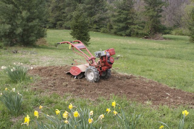 The rototiller follows the post-hole digger